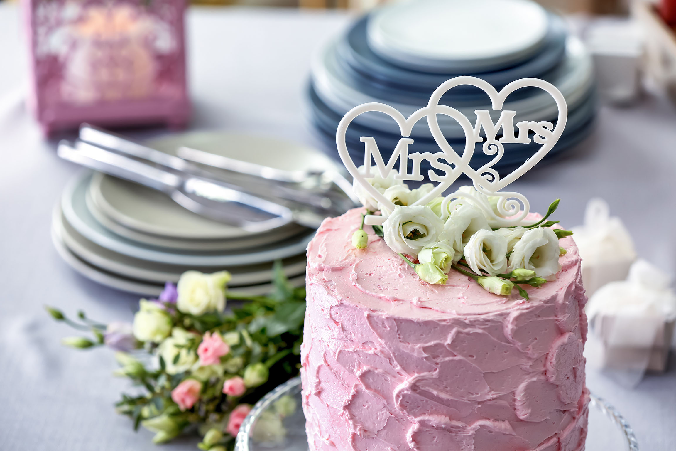 Delicious cake decorated with flowers and hearts for lesbian wedding