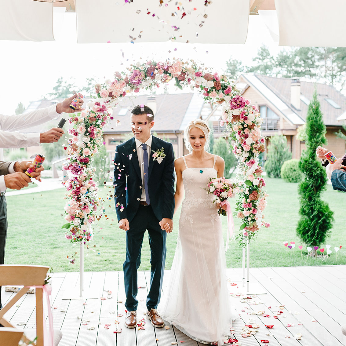 The bride and groom go through the arch, theirs sprinkled with leaves of roses and colored confetti. Wedding ceremony decorated with flowers and greenery of the outdoor in backyard banquet area.
